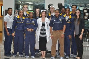 Coach Danielle O'Banion, left, and the Kent State basketball team visited Akron General Cancer Center and Dr. Laurie B. Matt-Amaral, center. Photo courtesy of Kent State Athletic Communications.