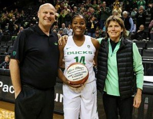 Jillian Alleyne is honored last month with a special commemorative ball for becoming Oregon's all-time rebounds leader in November. She eclipsed the record set by Bev Smith, right, in 1982. Duck coach Kelly Graves is at left. Photo by Eric Evans Photography, courtesy of Oregon Athletics.