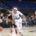 Jordin Canada fouls Minyon Moore.  Photo by Benita West, TGTVSports1.