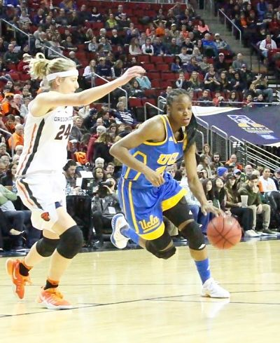 UCLA's Kennedy Burke takes the ball up court past Oregon State's Sydney Wiese in the Pac-12 Tournament semifinal game. Photo by Michael Houston/T.G.Sportstv1.