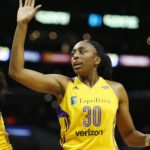 Chelsea Gray, left, gives a backwards-hand  high-five to Nneka Ogwumike. Photo by Maria Noble/WomensHoopsWorld.