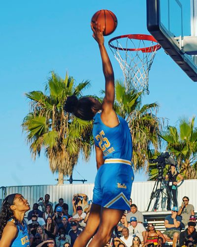 Monique Billings participates in a dunk contest when UCLA men's players earlier this month, while Jordin Canada looks on. Photo by Ted Chalfen/UCLA Athletics.