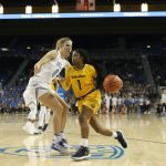 Asha Thomas drives by Chantel Horvat. Photo by Maria Noble/WomensHoopsWorld.