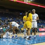 Monique Billings helps Jordin Canada to her feet. Photo by Maria Noble/WomensHoopsWorld.