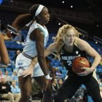 Annika Jank tries to keep the defense at bay. Photo by Maria Noble/WomensHoopsWorld.