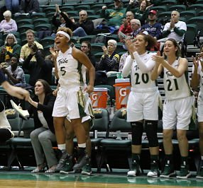 Misha Jones, left, and teammates celebrate a basket. Photo courtesy of William&Mary Athletics.