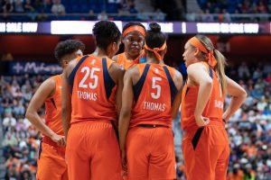 Jonquel Jones and her teammates huddle at a pause in play. Chris Poss photo.