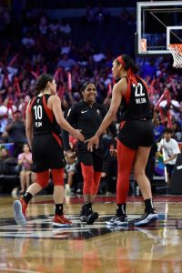 Sydney Colson walks to Kelsey Plum and A'ja Wilson after the Sparks call a timeout. NBAE via Getty Images photo.