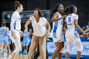 Coach Felisha Legette-Jack celebrates with players as a timeout begins. Photo courtesy of Buffalo Athletics.
