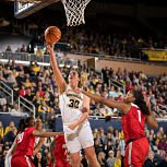 Hallie Thorne drives by the defense to score. Photo courtesy of Michigan Athletics.