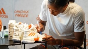 Candace Parker signs a pair of her new performance shoes for a fan. Photo courtesy of Adidas.