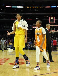 Candace Parker and daughter Lailaa, wearing her mother's college jersey, walk off court after Thursday's win. (Maria Noble)